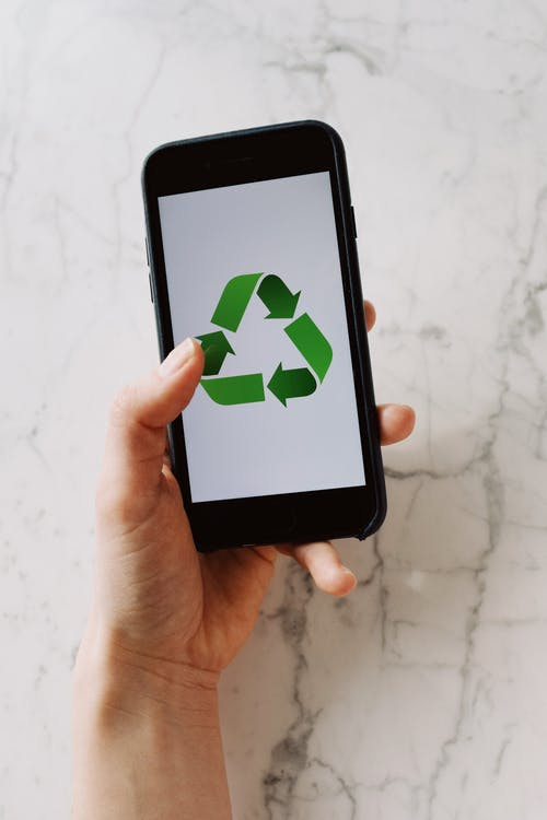 Anonymous crop person holding smartphone with recycle symbol