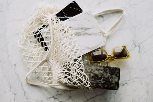 Top view of stylish sunglasses with marble notebooks arranged in eco friendly mesh sack on white marble surface