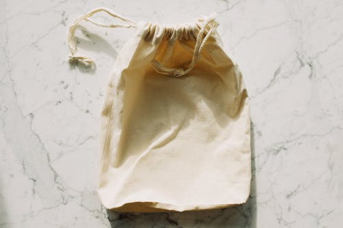 White textile bag with drawstrings placed on marble table