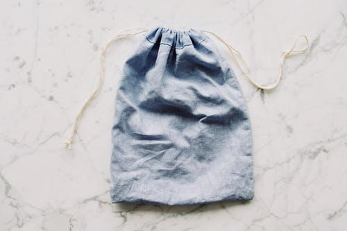 Top view of blue empty fabric reusable bag with white drawstrings placed on marble surface in light room