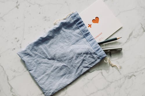 White postcard with pen and pencil in blue textile bag placed on marble table