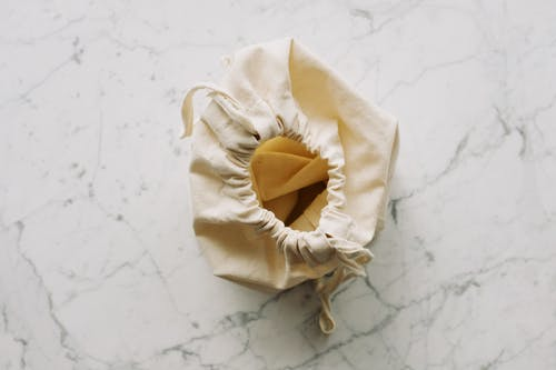 Empty white textile bag placed on marble table in room