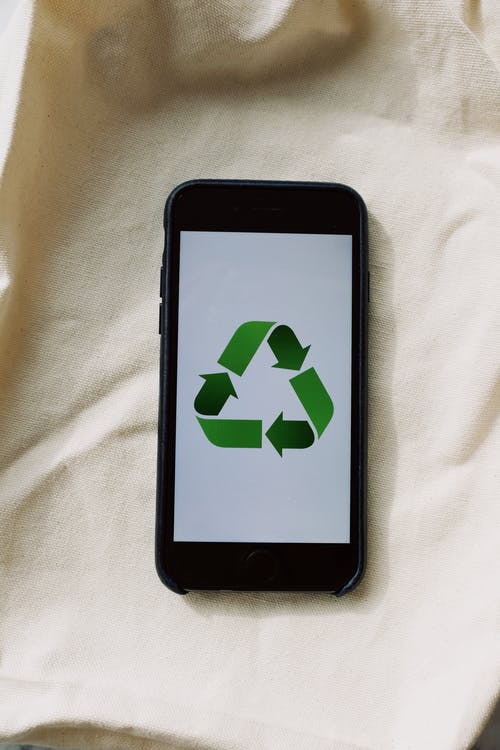 Smartphone with recycling symbol on screen placed on white textile surface