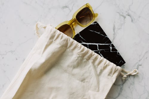 Trendy sunglasses and notepad in cotton eco friendly sack
