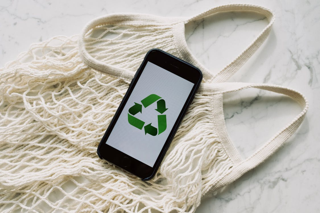 Smartphone with recycling sign on screen placed on white mesh bag on marble table