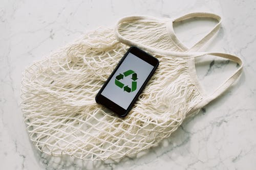 Overhead of smartphone with simple recycling sign on screen placed on white eco friendly mesh bag on marble table in room