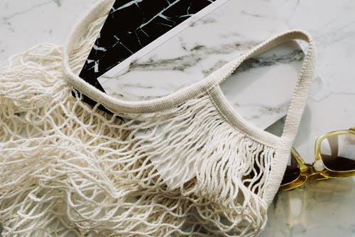 From above view of trendy sunglasses and books in eco friendly cotton mesh bag on marble table in room
