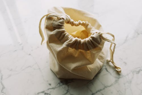 Top view of plain white fabric sack with drawstrings placed on marble table in room