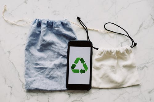 From above view of smartphone with recycling symbol on screen placed between white and blue textile bag on marble table in room