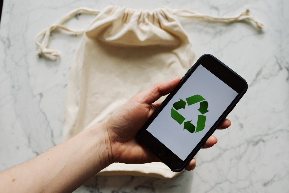 Faceless person showing recycle symbol on mobile phone screen