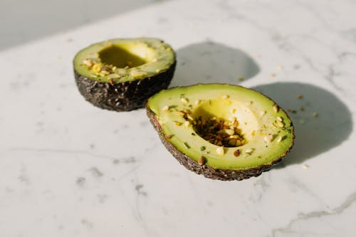 From above of fresh green avocado halves without kernels sprinkled with seed mixture placed on white marble desk served for healthy vegetarian breakfast preparation