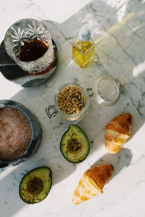 Healthy breakfast with croissants and avocado on marble table