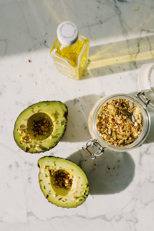 Delicious halved avocado with various seed grains and olive oil on marble surface