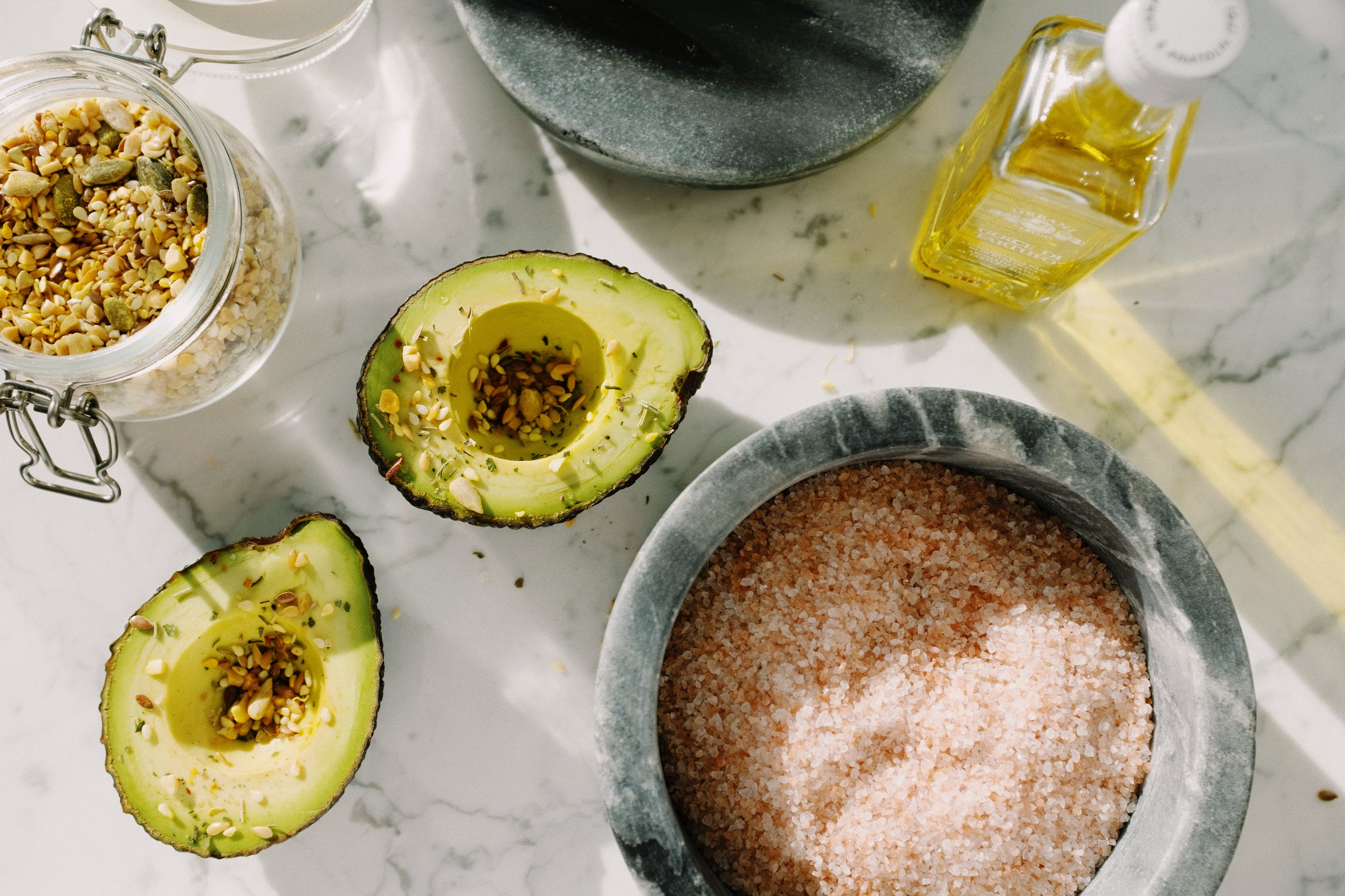 Fresh avocado halves with seed mix and other ingredients for healthy breakfast