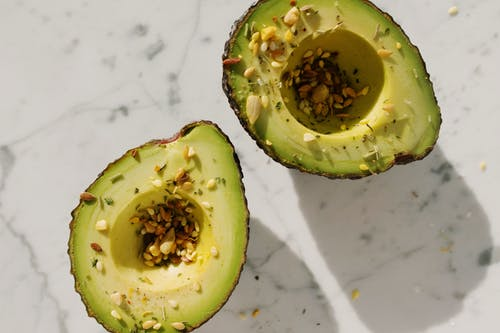 Top view of fresh green halved avocado without kernel with seed mixture on them placed on white marble table for healthy vegetarian breakfast