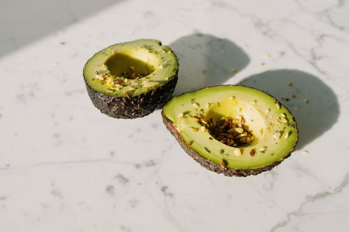 From above of green halved avocado sprinkled with various seeds placed on white marble counter served for healthy vegetarian breakfast preparation