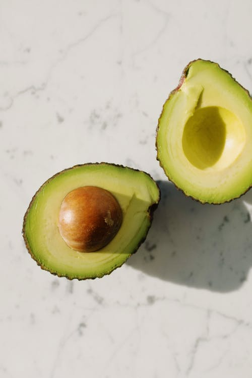 Halves of fresh green avocado on marble surface