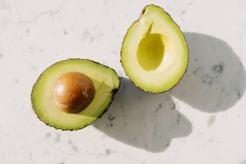 Sliced Avocado Fruit on White Surface