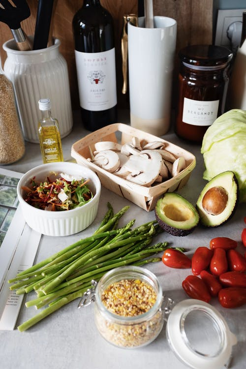 Healthy ingredients composition of vegetables near wine and utensils on table in kitchen