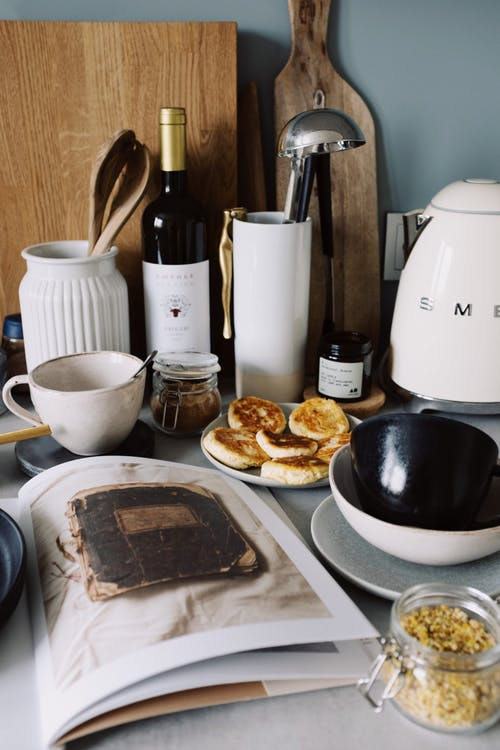 Top view of various types of tableware open cookbook and delicious homemade curd pancakes placed on table in cozy kitchen