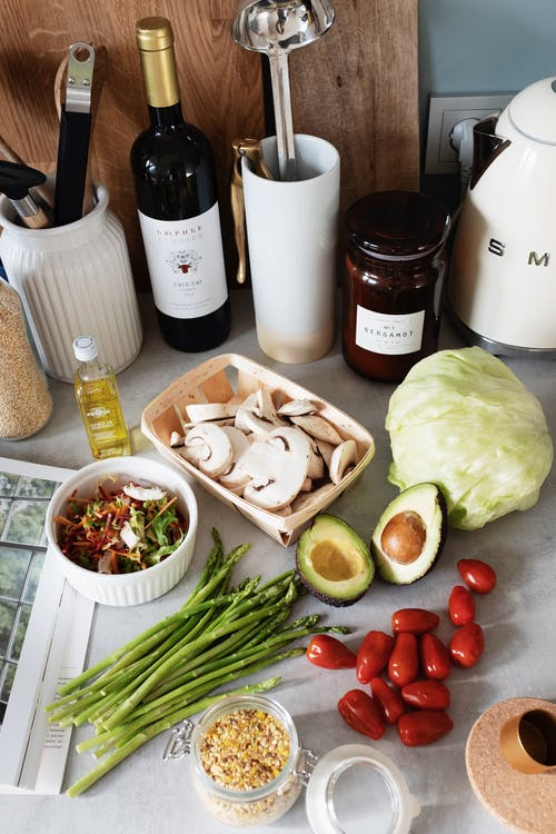 Top view of assorted healthy food and vegetables placed on tabletop near wine and utensils during home preparation for lunch