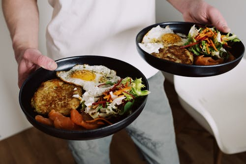 Crop man holding plates with fried eggs and salad