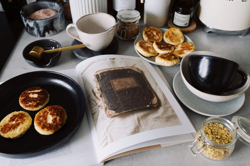 Fresh pancakes on black plate near opened book on kitchen table