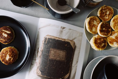 Fresh cheese pancakes served on plates near opened book on table in kitchen