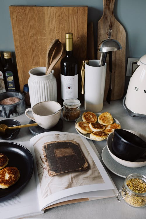 Delicious pancakes served on plates near opened book on table with various kitchenware and bootle of wine near cutting boards in light modern kitchen