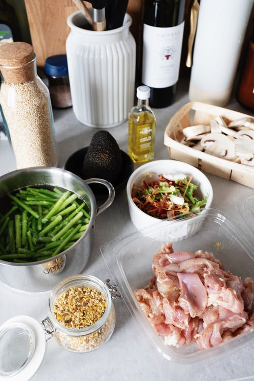 From above of raw chicken pieces in container green beans in pot of water and chopped champignons slices in wicker basket next to salad bowl avocado and spices in glass jar on countertop with various kitchen utensils