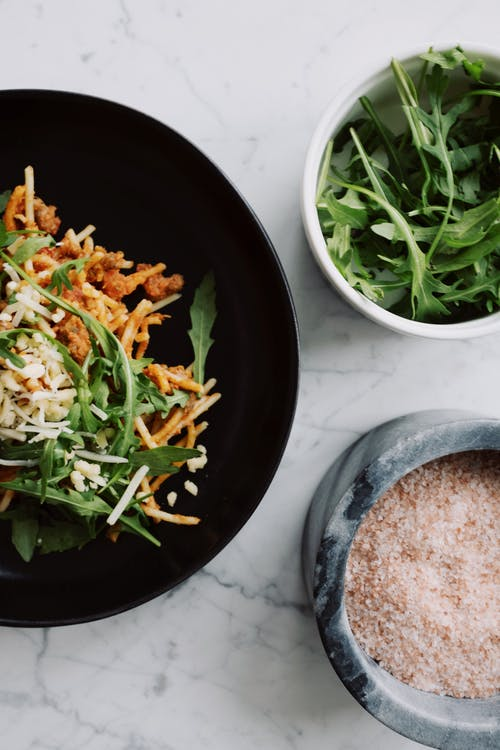 Delicious pasta Bolognese with arugula and pink salt