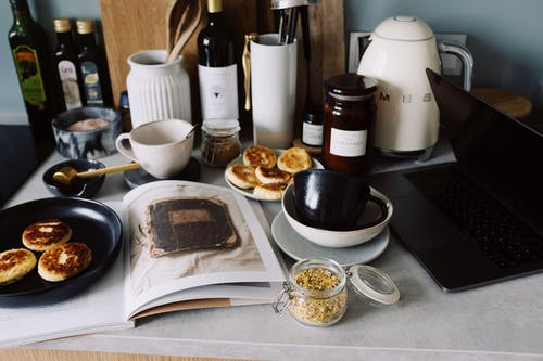 Countertop with various kitchenware cheese pancakes and laptop