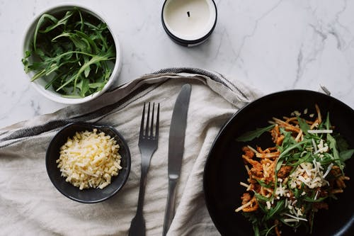 Appetizing meal served with cheese and arugula on table