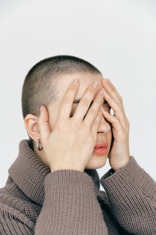 Woman In Sweater Covering Face With Hands