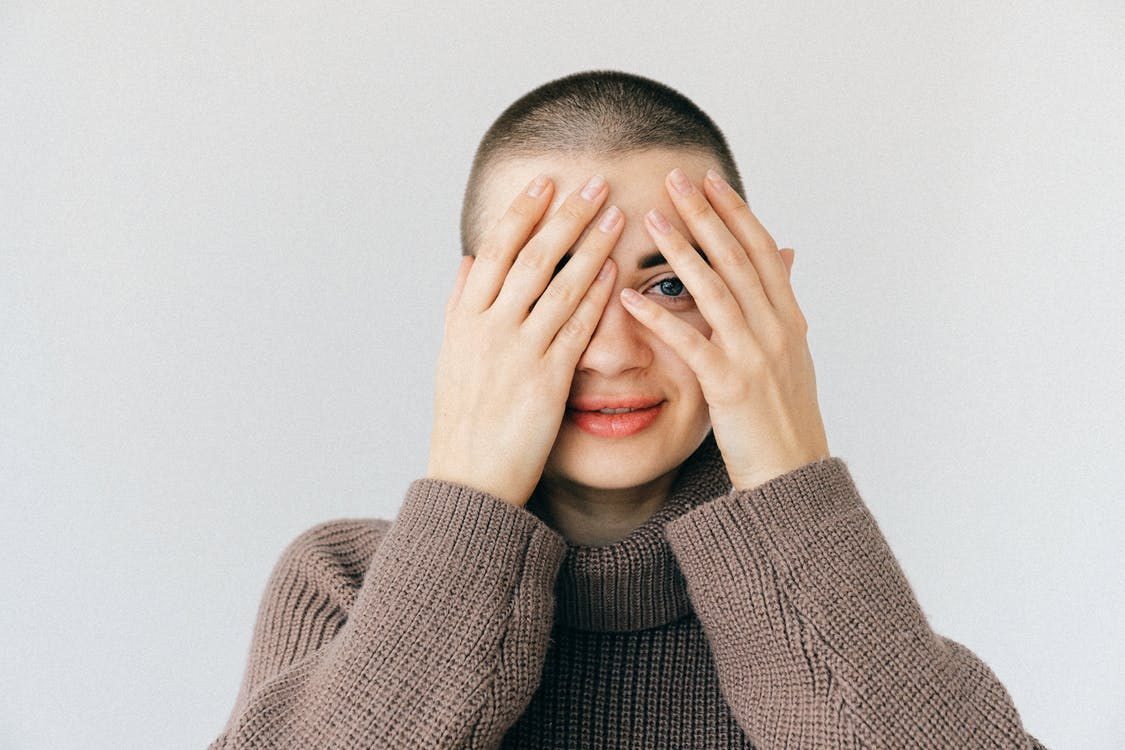 Woman in Brown Turtleneck Sweater Covering Her Face