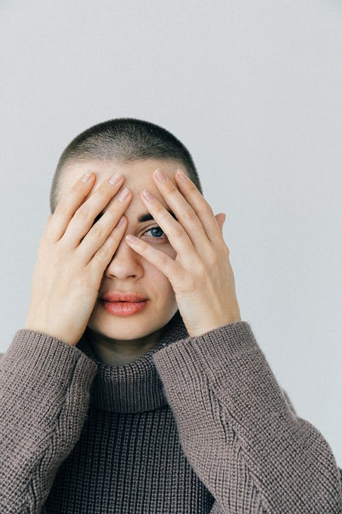 Woman with Short Hair Wearing Gray Knit Sweater Covering Her Face