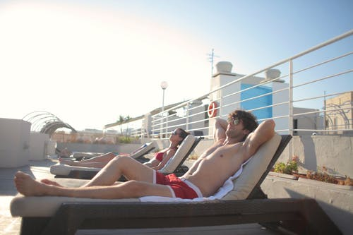 Side view of young man and woman in swimsuits and sunglasses relaxing on sun loungers together and enjoying summer sunny day during vacation