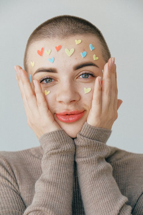 Young positive woman with many stickers on face