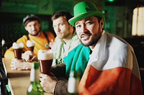 Man in Green Hat Holding Beer