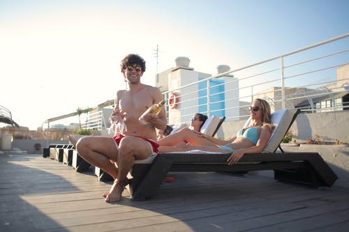 Smiling guy in swimwear and sunglasses sitting on lounger near girlfriend holding bottle of white wine in one hand and four glasses in another and looking at camera while chilling with friends
