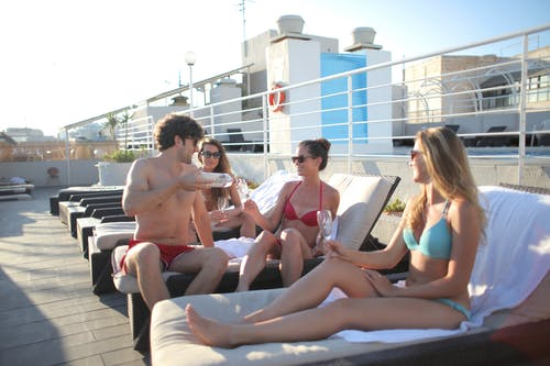 Young friends having fun on terrace of hotel together