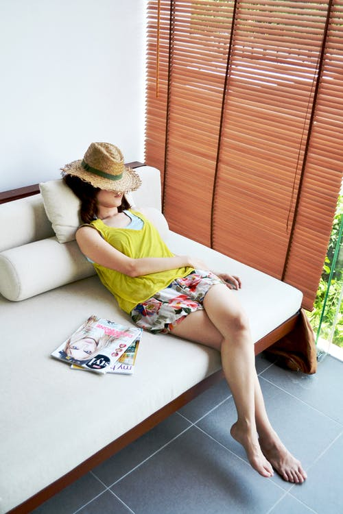 Woman In Yellow Top And Brown Sun Hat Sitting On Couch