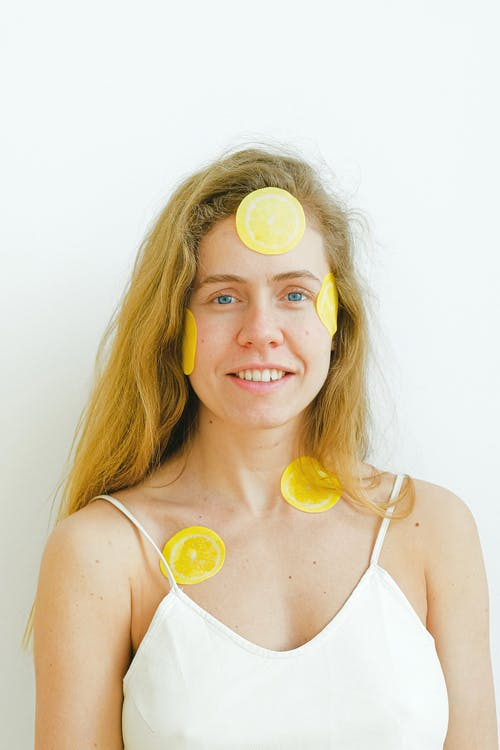 Optimistic female with slices of fresh lemon patches on face smiling and looking at camera while having skincare procedure during weekend