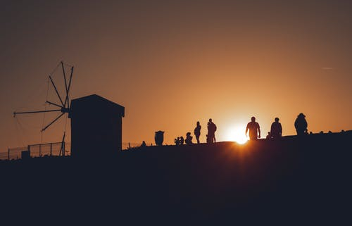 Silhouette of People Standing on Field during Sunset