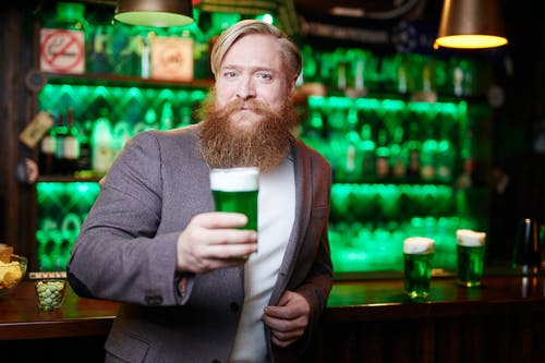 Bearded Man in Gray Suit Holding Green Beer