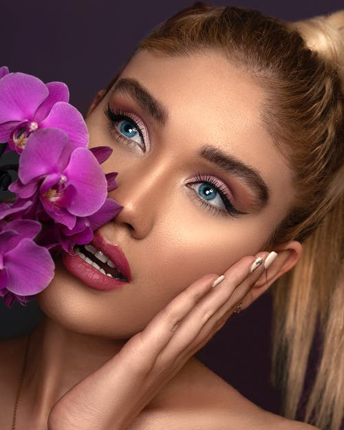 Close -up Photo of Woman With Pink Lipstick Holding Purple Flowers