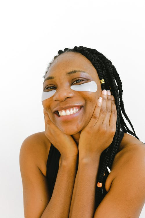 Ethnic smiling woman with eye patches and hands on cheeks