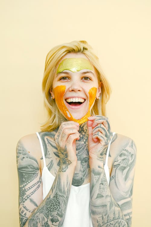 Young cheerful female with tattooed body and blond hair removing peel off golden mask from face looking at camera