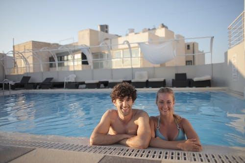 Topless Man Sitting on Swimming Pool Besides a Lady in Blue Bikini