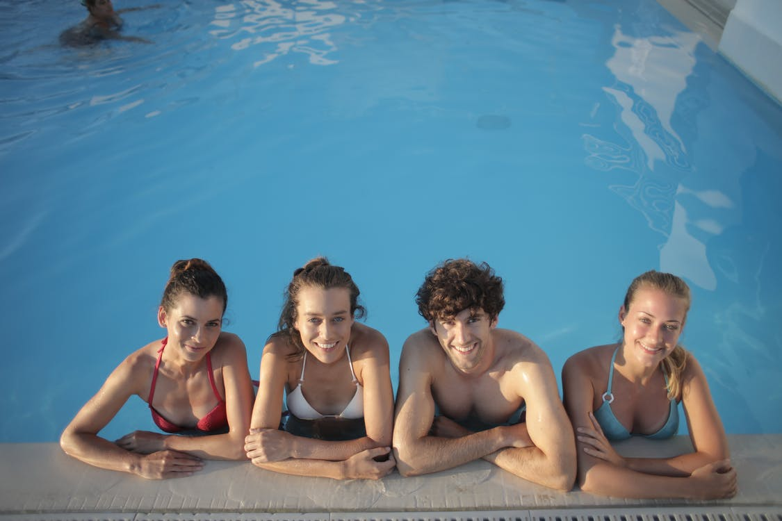 A Group pf Friends Sitting on Swimming Pool